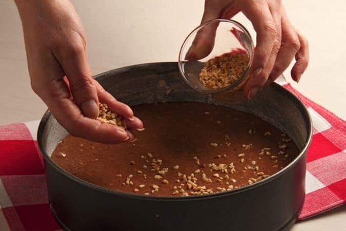 Versa l'impasto in una tortiera unta e infarinata e cospargi la superficie con la granella di nocciole rimasta.