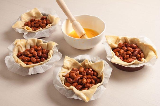 Bucherella il fondo di pasta con una forchetta, riempi con fagioli secchi e spennella il bordo con l'uovo leggermente sbattuto.