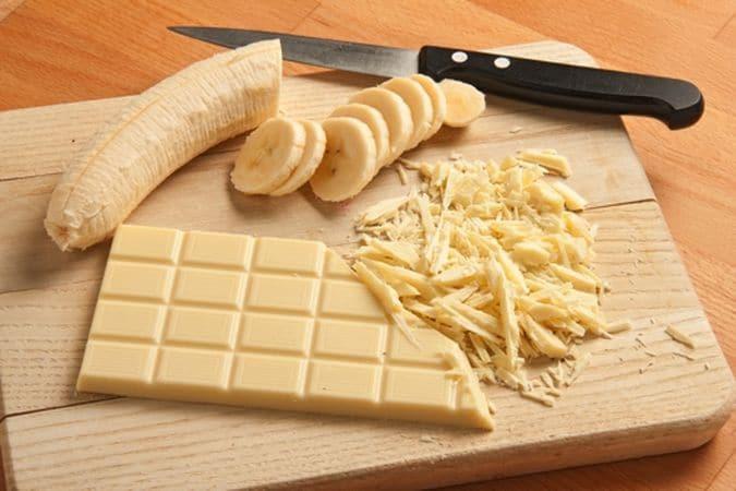 Sbuccia e affetta la banana e trita grossolanamente, con un coltello, il cioccolato bianco.