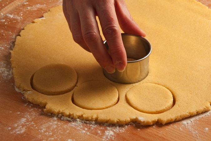 Riprendi la pasta e stendila, sulla spianatoia leggermente infarinata, a uno spessore di cinque millimetri circa poi con un taglia biscotti ricavane quanti più dischi puoi e disponili sulla placca del forno, rivestita di carta forno.
