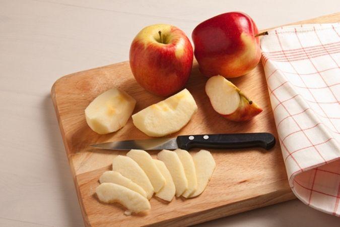 Dividi le mele in quarti, sbucciali ed elimina il torsolo poi affettale.