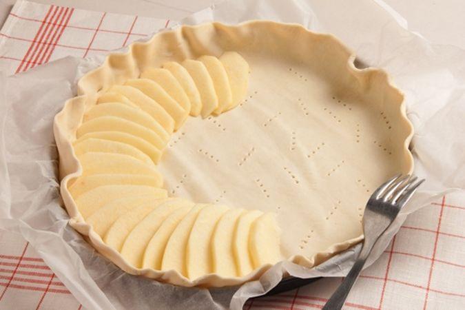 Stendi, in una tortiera a bordo basso, la pasta sfoglia con il suo foglio di carta forno e disponivi le fettine di mela, leggermente sovrapposte,