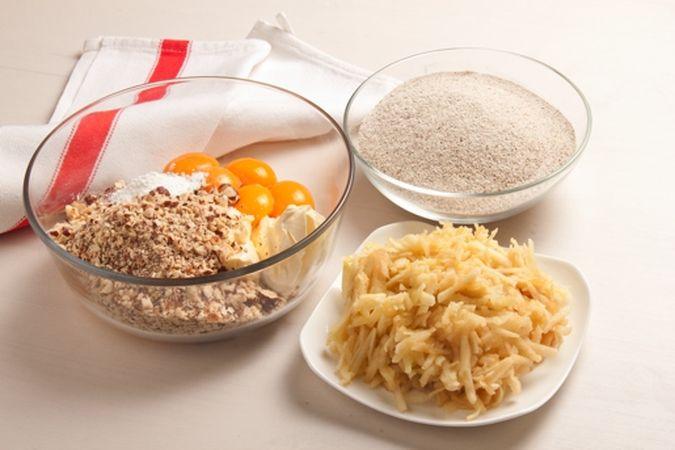 Ungi con una noce di margarina la tortiera, infarinala e scuoti via la farina in eccesso.<br /> Mescola in una ciotola la farina con lo zucchero, la margarina ammorbidita a temperatura ambiente, i tuorli, le nocciole tritate, la scorza di limone, il lievito e le mele grattugiate,