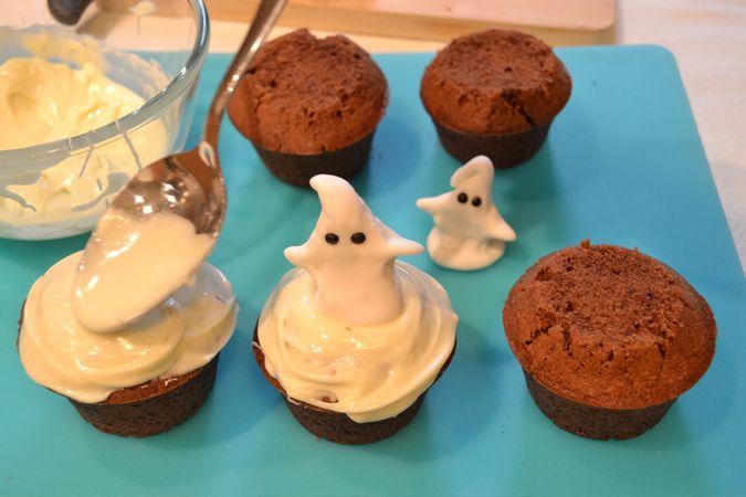 Fate sciogliere il cioccolato a bagnomaria, poi unite lo zucchero a velo setacciato e mescolate bene. Spuntate le tortine in modo che la parte superiore sia piatta e fare colare un cucchiaio abbondante di cioccolato fuso su ogni tortina; se necessario, aggiustate la copertura col dorso del cucchiaio. Fate aderire un fantasmino su ciascuna torta mentre il cioccolato è ancora liquido e lasciate seccare per almeno 2 ore