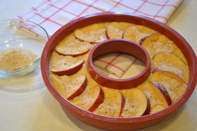 Versate in uno stampo a ciambella (diametro 24 cm) unto con margarina, poi disponete le fettine di mela con la buccia sulla superficie e cospargete con la granella di nocciole che avete messo da parte. Infornate per 45 minuti circa (fate la prova stecchino)