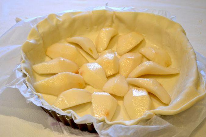 Adagiate la pasta sfoglia, utilizzando la carta in cui è avvolta, in uno stampo da crostata (26 cm di diametro) e sistemate le fette di pera sulla pasta