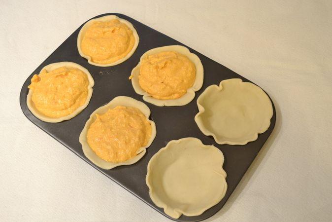 Tagliate 6 dischi di pasta e adagiateli su uno stampo da tartellette unto con margarina. Versate 2 cucchiai circa di composto in ogni crostatina