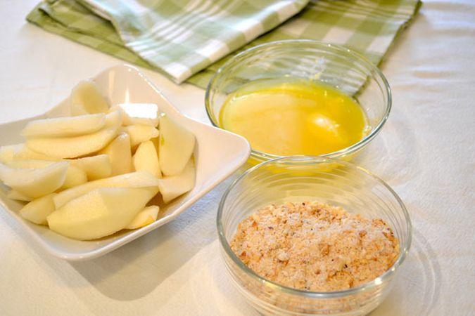 Accendete il forno a 180 gradi; pesate lo zucchero e toglietene 2 cucchiai che metterete in un mixer con le nocciole: tritate le nocciole non troppo finemente e mettete da parte. Sbucciate le pere, tagliatele in quarti e tagliate ogni quarto a metà. Fate fondere la margarina a bagnomaria o nel microonde