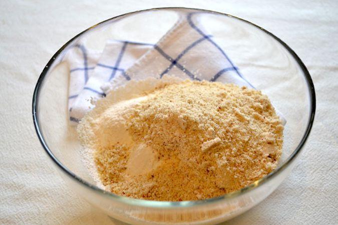 Accendete il forno a 200 gradi. Tritate finemente le mandorle; unite lo zucchero a velo e l'amido di mais e mescolatelo alle mandorle. Sciogliete la margarina a bagnomaria o nel microonde)