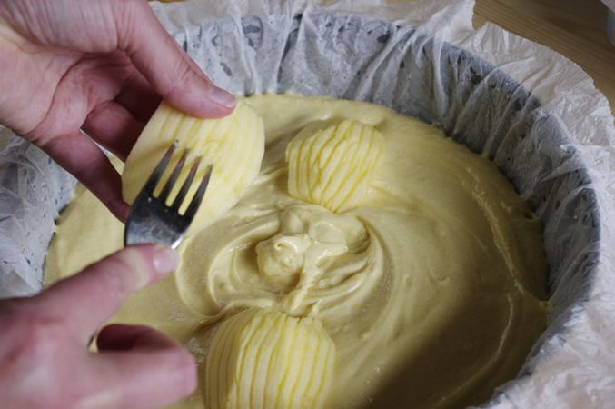 Versarlo nello stampo. Tagliare a quarti le mele, sbucciarle, togliere i torsoli e scalfire la parte esterna con una forchetta