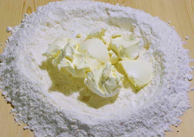 Mescolare le farine con il sale e lo zucchero, formare una fontana nel piano di lavoro e mettere nel centro Vallé&Burro