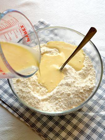Unite lo zucchero e mescolate. A parte, sbattete leggermente l'uovo e mescolatelo alla panna. Unite al resto degli ingredienti e mescolate. Impastate brevemente e formate una palla che avvolgerete con cellophane per poi metterla in frigo per un'ora