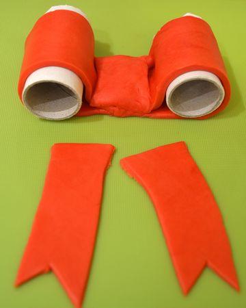 """Mentre il dolce si raffredda, preparate le decorazioni. Colorate 1/3 della pasta di zucchero di verde e il resto di rosso. Stendete la pasta rossa tra due fogli di carta forno e ricavate un nastro lungo 20 cm circa e alto 5, un rettangolo di 5 x 3 cm e due nastri di 10 cm x 5. Ripiegate le estremità del nastro più lungo verso il centro, facendole combaciare a metà della lunghezza. Aiutatevi con un oggetto cilindrico ben spolverato di zucchero a velo (qui ho usato un rotolo di carta su cui era avvolto il cellophane, ma va benissimo un  cilindretto di carta forno, che toglierete prima di decorare la torta) per mantenere la forma del fiocco (vedi foto). Adagiate il rettangolo più piccolo (quello 5x3) nel centro del fiocco, a simulare il nodo, e fatelo aderire con una leggera pressione. Modellate i lembi del fiocco a vostro piacimento (io li ho tagliati a V) e, se volete, imprimete una cornice lungo tutto il bordo del fiocco con una forchetta per dare un """"effetto tessuto"""".  Adagiate su un foglietto di carta forno e mettete da parte"""