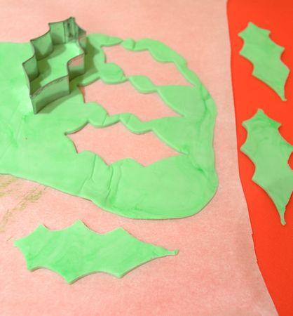 Per modellare le foglie, stendete la pasta verde tra due fogli di carta forno, poi ritagliate l'agrifoglio  con uno stampino: lo stampo che ho usato qui è lungo 7 cm e largo 3, e per questa torta ho ricavato 10 foglie; se il vostro stampo è più piccolo ne dovrete ricavare di più