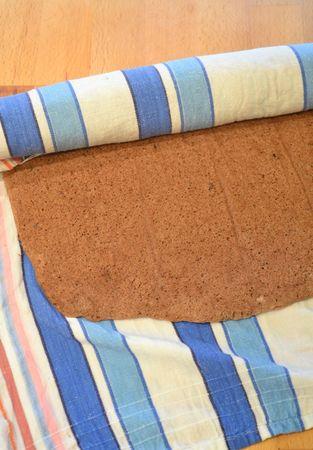 Bagnate uno strofinaccio pulito, strizzatelo bene e stendetelo sul tavolo. Rovesciate con delicatezza la pasta biscuit ancora calda sullo strofinaccio, staccate la carta forno e arrotolate immediatamente. Lasciate raffreddare completamente in questo modo (almeno un'ora, ma meglio due)