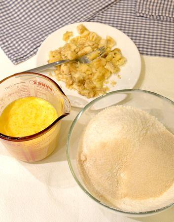 Mescolate la farina e il lievito e setacciateli, poi unite 80 gr di cocco e 100 gr di zucchero (tenete da parte 30 gr di zucchero e 20 gr di cocco, serviranno alla fine) e la scorza grattugiata del limone. Fate sciogliere la margarina a bagnomaria o nel microonde e unitela al latte, poi sbattete le uova (non troppo) con gli ingredienti liquidi. Sbucciate le banane e schiacciatele con una forchetta. In questo modo avrete tre gruppi di ingredienti: i solidi, il liquidi e la frutta