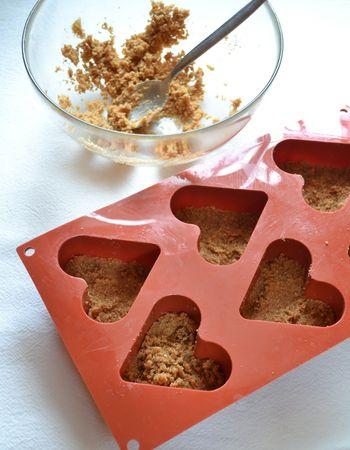 Tritate i biscotti nel mixer. Fate sciogliere (a bagnomaria o nel microonde) la Vallé+Burro e mescolatela con i biscotti  tritati. Fate cadere un cucchiaio abbondante di questo composto in ogni stampino e premete bene con le dita per compattarlo. Mettete in frigo per un'ora a compattare