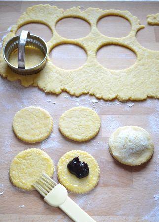 Trascorso il tempo di riposo, accendete il forno a 180 gradi. Stendete l'impasto sul piano di lavoro infarinato e ricavate tanti dischi di pasta (possibilmente con uno stampo dentellato). Mettete un cucchiaino di marmellata nel centro di metà dei dischi, spennellate il bordo con uovo sbattuto e fate aderire un altro disco di pasta con una leggera pressione delle dita, in modo da formare un tortello