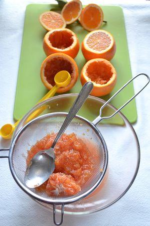 Tagliate la calotta e svuotatele con l'aiuto prima di un coltellino affilato, poi di un cucchiaio o di uno scavino (un attrezzo normalmente usato per ricavare palline di frutta). Raccogliete la polpa a parte filtrandola con un colino. Togliete bene la polpa ma state attenti a non perforare la buccia. Imbottite ogni arancia con carta da cucina accartocciata (devono essere ben asciutti all'interno) e capovolgete i frutti. Mettete da parte