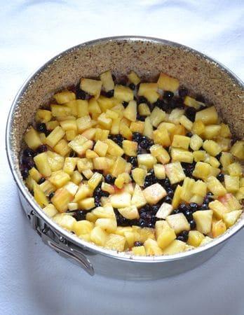 Foderate il fondo di una tortiera a cerchio apribile da 22 cm con carta forno e ungete i bordi. Inclinate la tortiera e versate le noci tritate sul bordo, poi fate ruotare la tortiera inclinata in modo che le noci si attacchino al bordo ricoprendolo completamente. Scrollate via gli eccessi e spargete i 15 gr di zucchero rimasti sul fondo dello stampo e disponete la frutta sopra lo zucchero in modo da non lasciare spazi vuoti