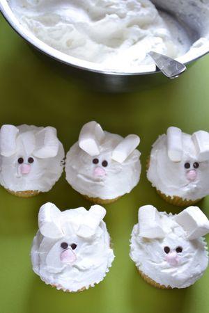 Spalmate un cucchiaio abbondante di panna montata su ogni tortina, poi conficcate i pezzi di marshallow bianco nella panna per formare le orecchie del coniglio. Usate le gocce di cioccolato come occhi, poi appallottolate un pezzetto di marsmallow rosa ed ecco il naso