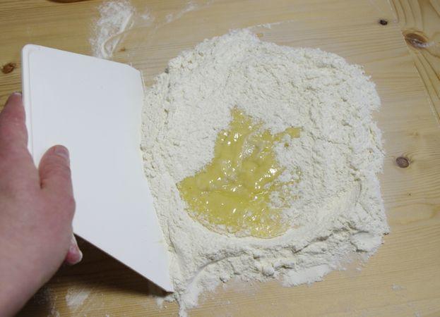 Mettere nel centro le uova e la scorza di limone e d'arancio