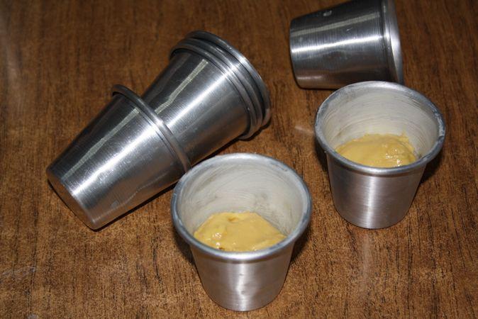 Imburrare e infarinare gli stampi in allumino da babà (20 pezzi) e riempirli con l'impasto per metà