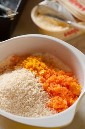In una ciotola unite la farina e il lievito setacciate, le carote, le mandorle, la buccia grattugiata delle arance e un pizzico di sale