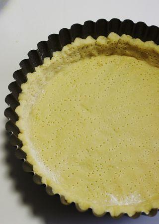 Fare raffreddare mescolando spesso. Quindi mettere in frigo. Riprendere la frolla, stenderla ad uno spessore di ½ cm e rivestire uno stampo a fondo rimovibile di 20 cm di diametro alla base. Bucare bene con una forchetta