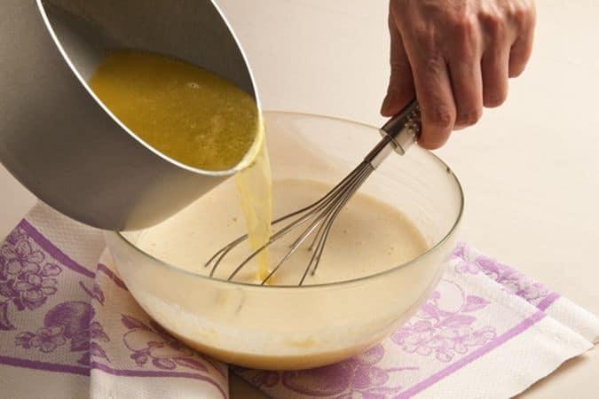 Sbatti i tuorli con lo zucchero, aggiungi la farina e diluisci con il composto di margarina e acqu
