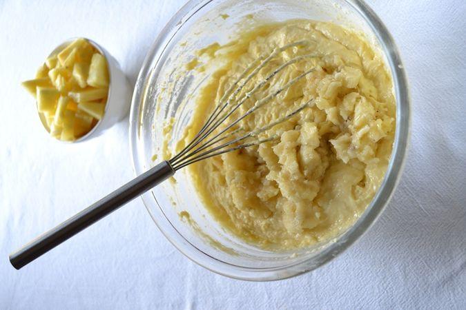 Schiacciate la banana e unitela all'impasto, poi mescolate bene; se l'impasto vi sembra troppo asciutto aggiungete un po' di latte (senza diluire troppo), poi aggiungete l'ananas a pezzetti e mescolate ancora