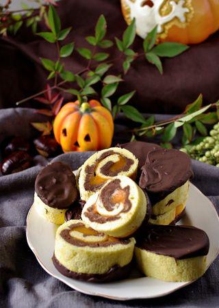 Tagliuzzare il cioccolato, metterlo in una ciotola e scioglierlo a bagnomaria. Tagliare il rotolo a fette di circa 3 cm, immergerle da un lato e mettere a rassodare su una gratellaBuoni dolci di Halloween da Morena e da Vallé ♥