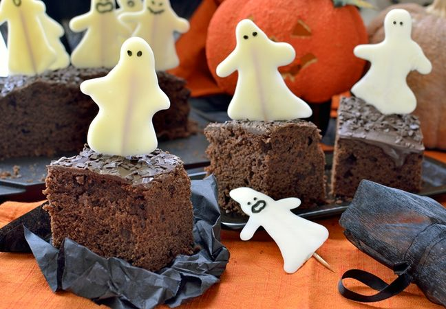 Staccate con cura i fantasmi dalla carta e decorate il lato piatto col pennarello alimentare, poi infilzate sulla torta