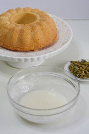 preparare la glassa sbattendo zucchero e acqua, in aggiunta limone e semi di cardamomo