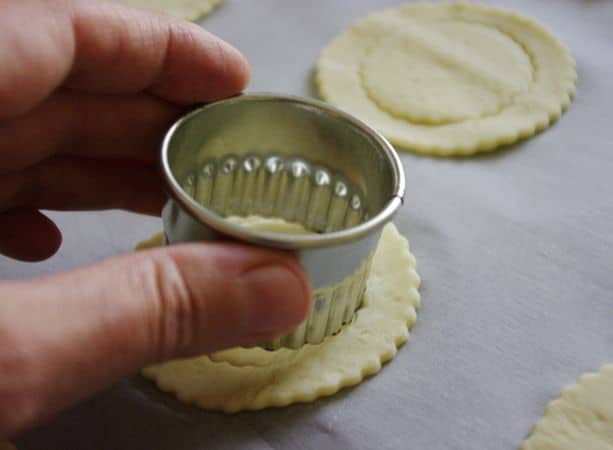 Tagliare con uno stampino 20 dischetti si circa 6 cm e posizionarli nella placca da forno. Con uno stampino più piccolo segnare dei cerchi in mezzo ai dischi tenendo però uniti due punti opposti.