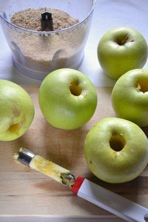 Tritate le noci nel mixer e mischiatele con lo zucchero di canna e un cucchiaino di cannella. Pelate le mele e privatele del torsolo con l'apposito utensile