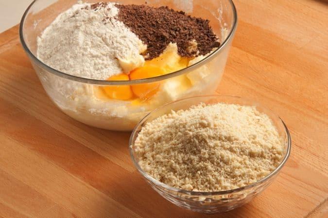 Lavora in una ciotola la margarina con lo zucchero e la vanillina, aggiungi la farina setacciata con il lievito, le uova, il cioccolato grattugiato, la scorza di limone e le mandorle ridotte in polvere;