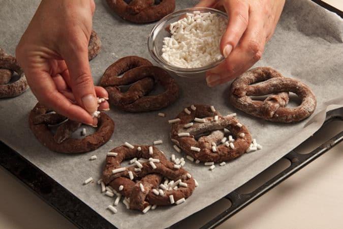 """Ripiegali in modo da dare la caratteristica forma dei """"bretzel"""" e disponili sulla placca del forno rivestita di carta forno."""