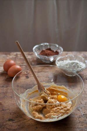 Lavorare la margarina ammorbidita con il miele fino ad ottenere un composto cremoso e liscio. Aggiungere le uova una alla volta. Setacciare la farina con il cacao ed incorporarla alla crema di uova e margarina mescolando delicatamente