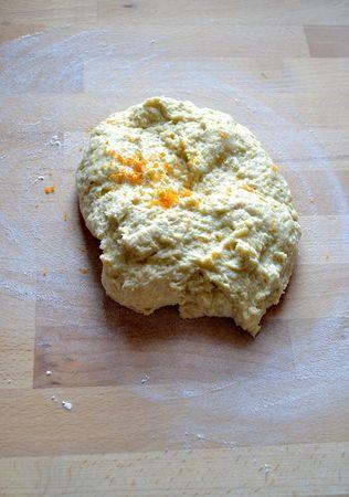 Versate il latte col lievito nella ciotola della farina, mescolate un poco, unite la Vallé sciolta e l'uovo e mescolate quel tanto che basta per amalgamare. Versate tutto sul piano di lavoro infarinato, unite la scorza di arancia grattugiata  e impastate per 10 minuti circa