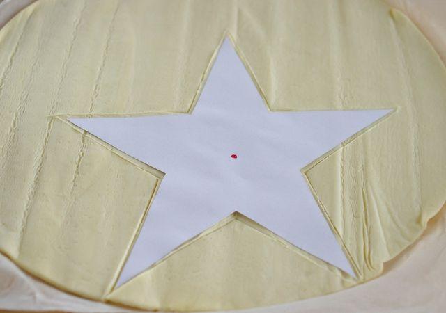 Intagliare su una base di sfoglia una stella di circa 15 cm posizionarla nella placca e bucherellarla con una forchetta o con l'apposito attrezzino