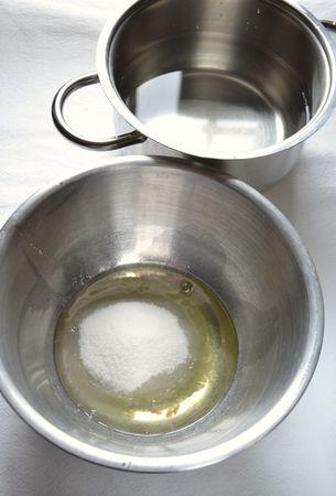 Mettete il contenitore con gli albumi sopra la pentola con l'acqua calda (il fondo non deve essere a contatto con l'acqua) e, tenendo il fuoco basso, frullate con un mixer finché il composto aumenta di volume e diventa lucido e compatto (ci vorranno circa 5 minuti)