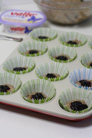 sistemare negli stampini da muffin un cucchiaio di composto e aggiungere al centro un cucchiaino di marmellata