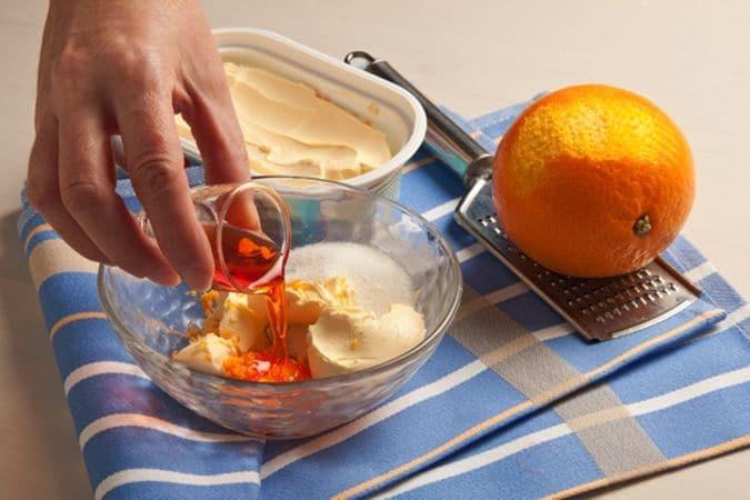 Metti in una ciotola la margarina e aggiungi lo zucchero, la scorza grattugiata di arancia e il liquore all'arancia, lavora il composto fino a renderlo omogeneo.