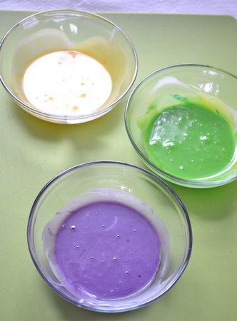 Quando il forno è in temperatura e la seconda lievitazione è terminata, infornate per 30 minuti circa (se il dolce si colorisce troppo coprite con stagnola, ma non prima dei 20 minuti). Sfornate e lasciate raffreddare sulla gratella. Quando il dolce è freddo, preparate la glassa: mescolate lo zucchero a velo col succo di limone (aggiungete pochissima acqua se necessario) fino a formare una glassa piuttosto fluida. Dividete in tre parti uguali e colorate di verde, viola e giallo