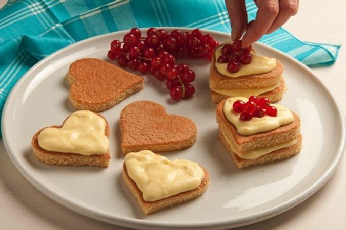 Incorpora la crema di margarina alla crema preparata ben fredda. Ritaglia, con un tagliapasta, i cuori di pan di Spagna, farciscili con la crema e decora con il ribes ed una spolverata di zucchero a velo.