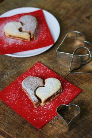 Farcire metà biscotto bianco con crema al cioccolato, metà biscotto al cacao con crema al cioccolato bianco. Servire con zucchero a velo