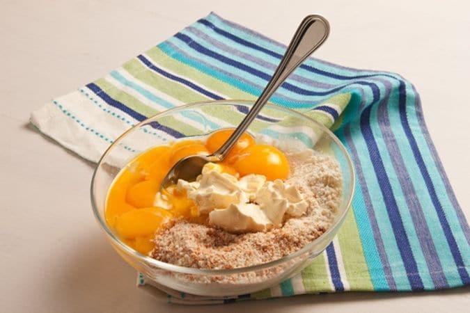 In una ciotola mescola la farina con i tuorli, la margarina ammorbidita a temperatura ambiente, gli amaretti sbriciolati e le mandorle ridotte in farina.