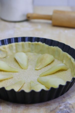 Stendere la base e foderare uno stampo cannellato (27cm). Ricoprire la base con lo zucchero di canna e sistemare le pere cotte precedentemente a vapore e divise in 4 parti