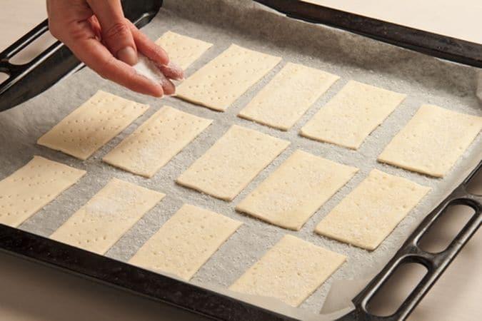 Ritaglia dalla pasta sfoglia 16 rettangoli; disponili sulla placca del forno, rivestita di carta forno, bucherellali con i rebbi di una forchetta e cospargili con lo zucchero semolato